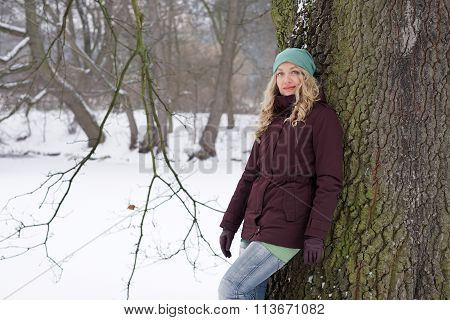 woman leaning against tree in winter landscape