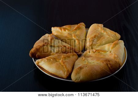 A plate with fresh pies on a black wooden table