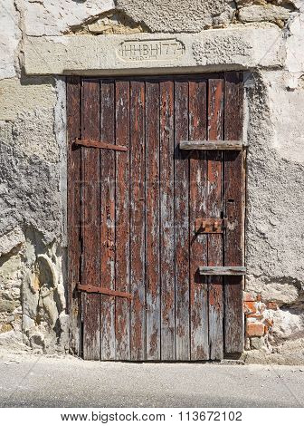 Old, heavily weathered, brown wooden door