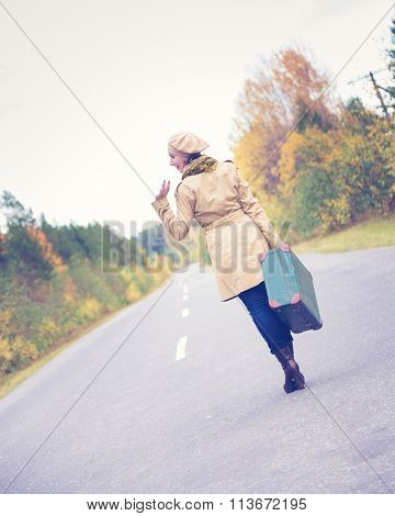 Elegant woman with a suitcase traveling the highway.
