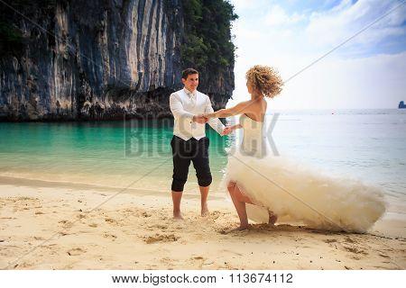 Groom Blonde Bride In Fluffy Dress Join Hands Swing On Beach