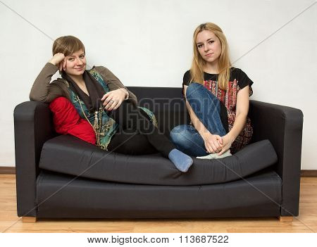 Women In Bright Dresses Are Sitting On The Black Sofa