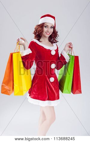 Sexy Caucasian Ginger Santa Helper Girl With Plenty Of Colorful Shopping Bags. Posing Against White