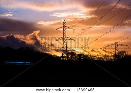 Industrial landscape with cables, train and sunset