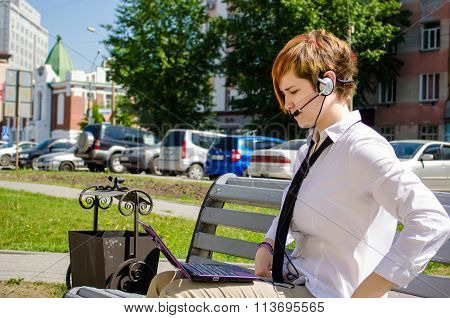 Young Business Woman With A Laptop Working Outdoor Sitting On The Bench