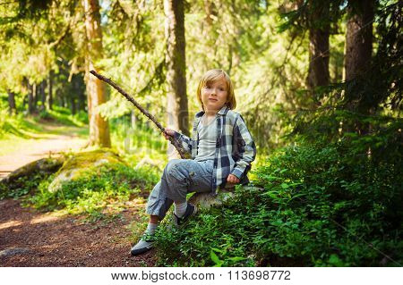Portrait of a cute little boy hiking in a forest