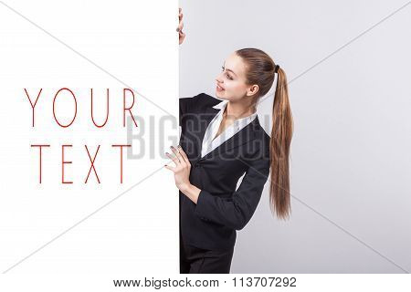 Girl In A Business Suit Stands Next To The Board For The Text And With A Smile Looking At The Camera