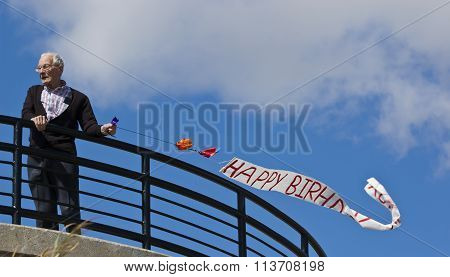 A grandfather flying a banner saying happy birthday