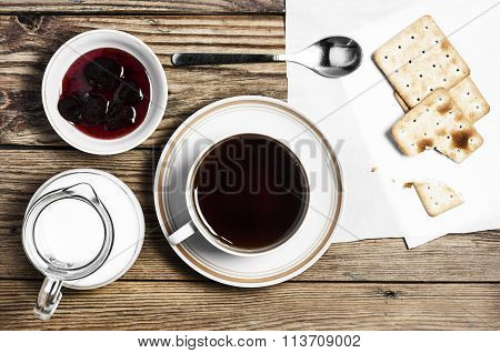 Close-up of a cup of tea, milk, some dry loaves and strawberry jam on a  wooden background in the ho