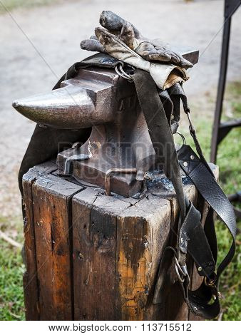 Worn iron anvil apron and gloves