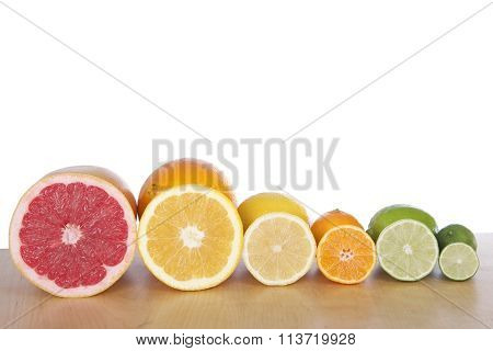 sliced citrus lined up in stacks on light brown wood table white background