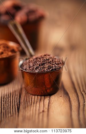 grated chocolate, powder and cocoa beans in vintage measuring copper pans  on old wooden background