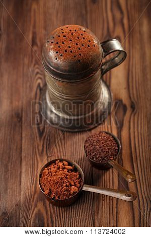 vintage sifter with cocoa powder and grated chocolate  in vintage measuring copper pans  on old wooden background
