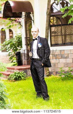 Handsome groom at wedding tuxedo smiling and waiting for bride.