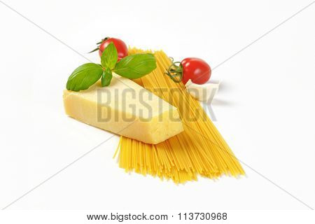 wedge of fresh parmesan cheese, vegetables and spaghetti on white background