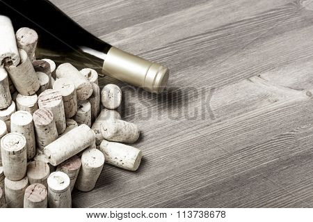 Wine bottle and wine corks on a wood background in horizontal format