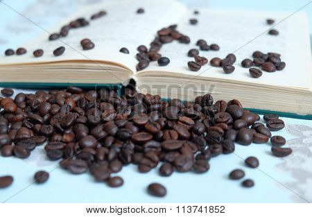 Roasted coffee beans on blurred background of an open book in pastel colours