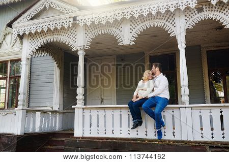 Husband And His Pregnant Wife Sitting On Porch