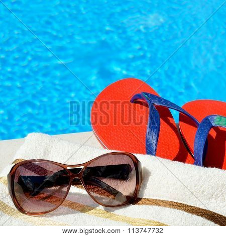 Sunglasses, Beach Towel And Flip-flops By The Swimming Pool.