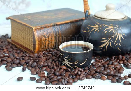 Cup of coffee, coffee beans, a teapot in the background of a closed book