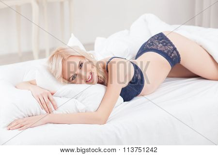 Cheerful young woman is relaxing in bedroom