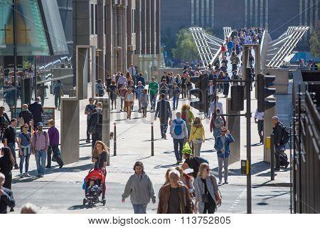 Lots of people walking in the City of London via millennium bridge