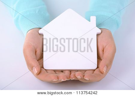 Female hands holding model of house, closeup