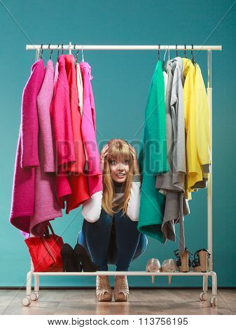 Scared Woman Hiding Among Clothes In Mall Wardrobe