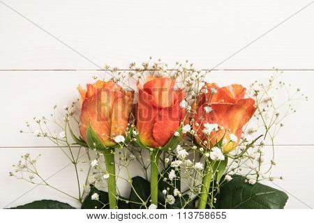 A Bouquet Of Orange Roses And Gypsophila On Wooden Table. Copy Space