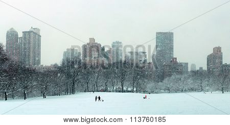 Central Park winter in snow with skyscrapers in midtown Manhattan New York City