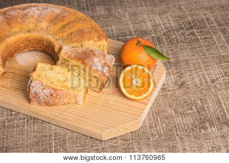 Slices Of Clementine Cake With Powdered Sugar Topping. Cake On A Board With Fresh Clementines On Woo