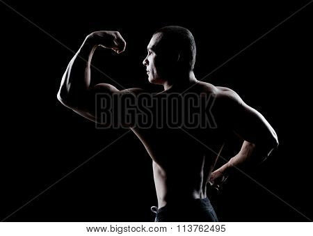 bodybuilder demonstrates biceps back view on a dark background