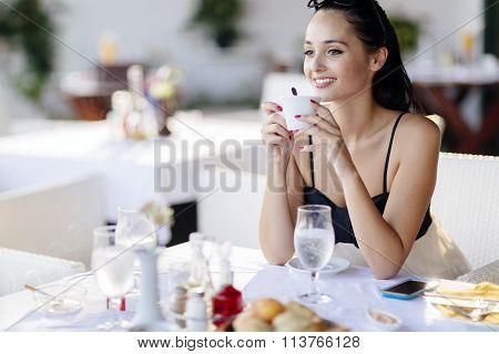 Beautiful Woman Drinking Coffee In Restaurant