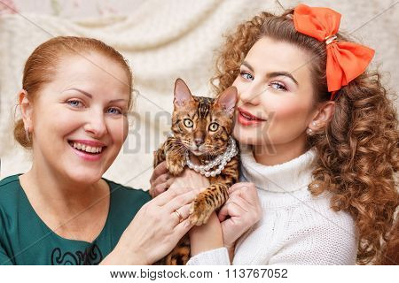 Mother, Daughter And A Cat. Cat In The Beads.
