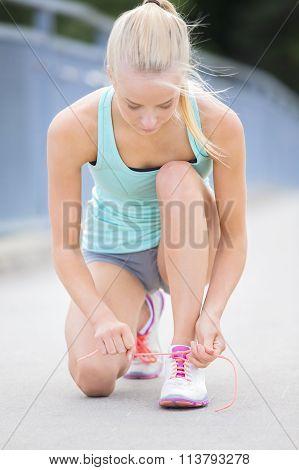 Slim woman runner tying shoelaces on bridge