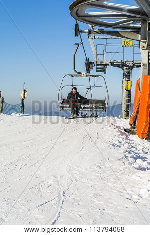 Snowboarder On The Bench Chairlift.