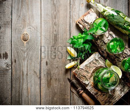 Cocktail On A Wooden Stand With Limes And Mint. Free Space For Text .