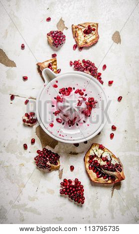 Juicer With Slices Of Pomegranate. On Rustic Background.