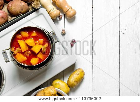 Stewed Potatoes With Meat And Spices In An Electric Cooker On White Wooden Table. Free Space For Tex