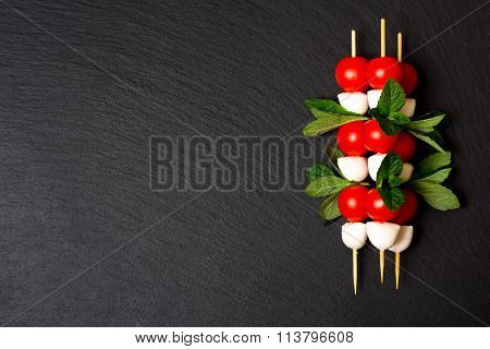 Caprese Salad On Sticks on a black background