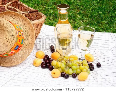 Wine, Fruits And Basket Of Picnic  On A Tablecloth