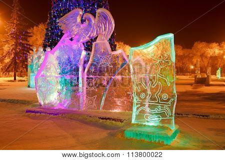 Ice sculpture in the city park on Christmas and New Year with cave paintings of deer, mythical creat