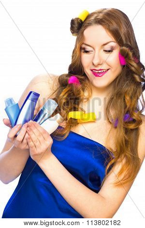 Beautiful Woman With Long Hair In Curlers Holding Products In Her Hands And Looking Down