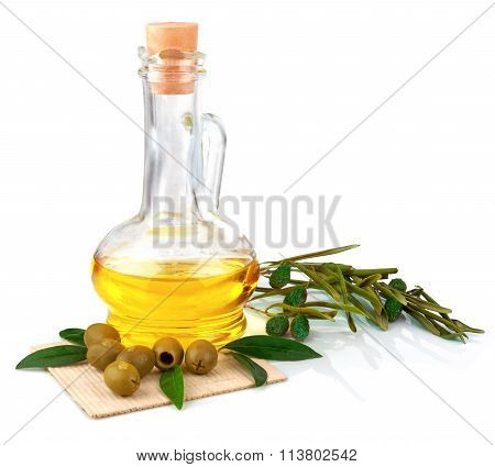 Glass Bottle Of Olive Oil With Olives And Leaves On The Mat