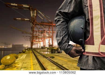 construction worker checking location site with crane on the background