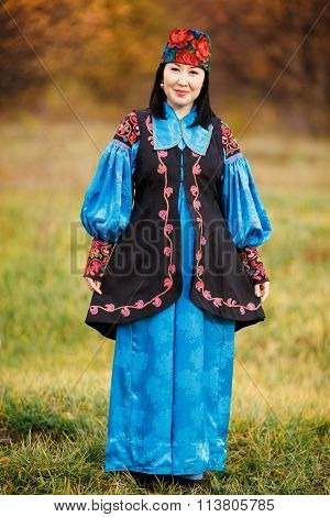 Beautiful girl in national dress smartly blue with ornaments and embroidery.