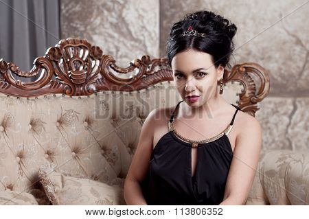 attractive young brunette sitting on  beautiful sofa, portrait close-up, gold eyeshadow