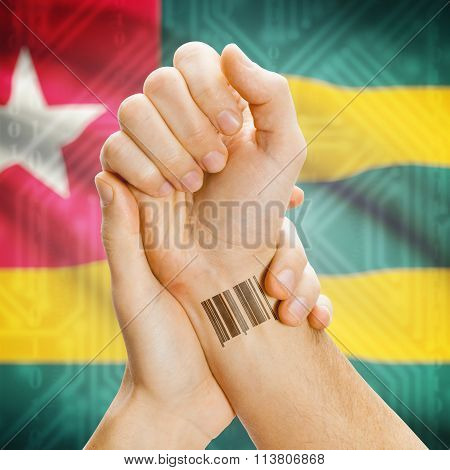 Barcode Id Number On Wrist And National Flag On Background - Togo
