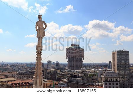 Cathedral statue and view of Milan cityscape with Torre Valesca