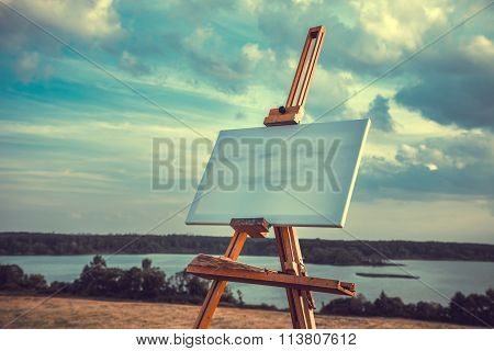 Blank Canvas Rests On A Easel On Lake Landscape, Retro Styled Photo.